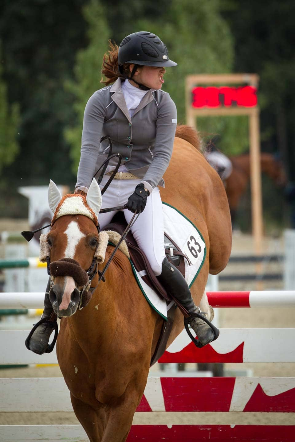 Professional female equstrian lands a big jump with timer in the background during Grand Prix competiton.
