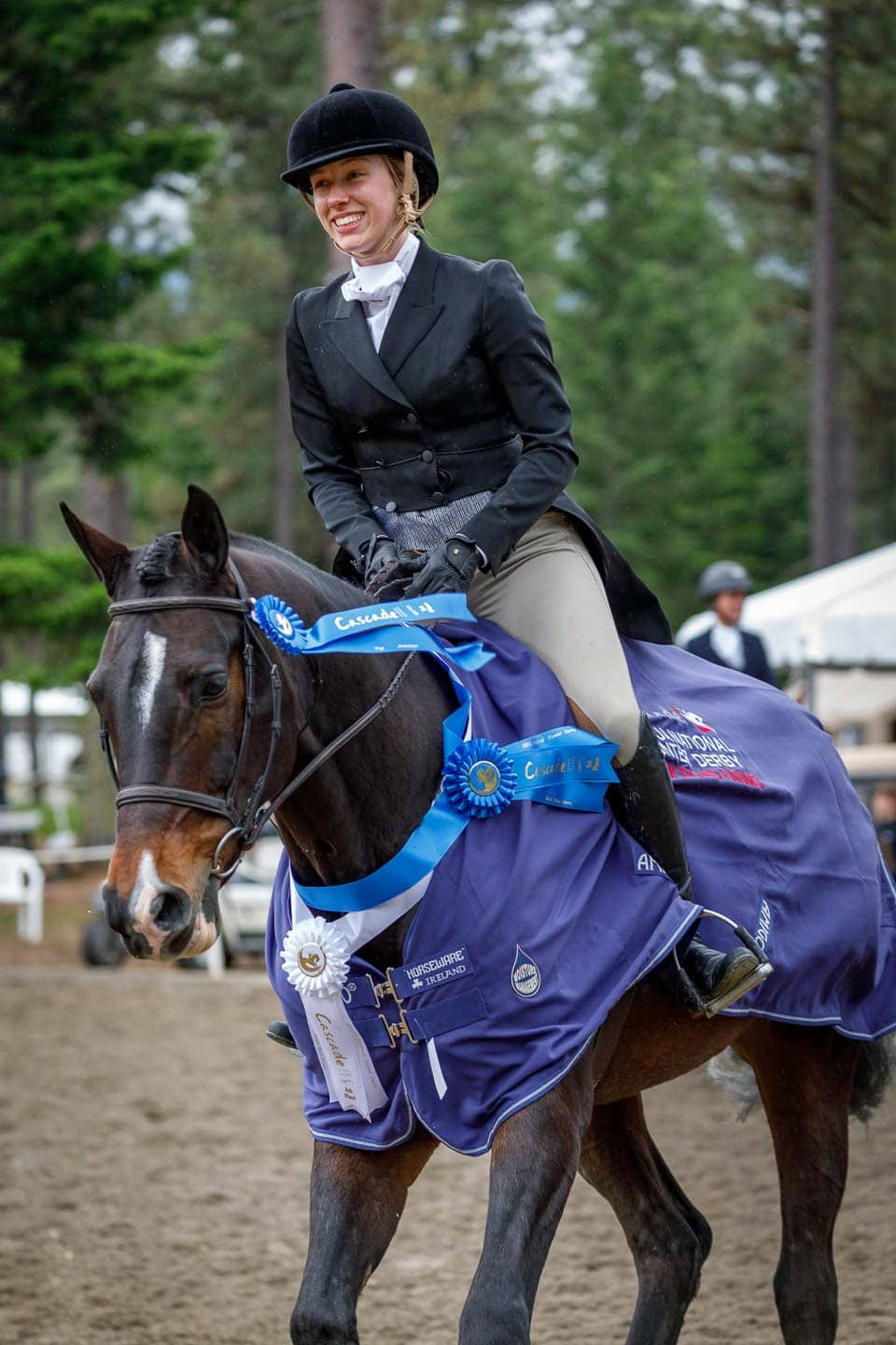 Female equstrian smiling while riding a victory gallop after winning the Cascade Grand Hunter Derby